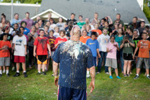 A youth pastor, covered in colorful cake and frosting, facing a wild and rowdy crowd of youth group students in the back.