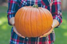 woman holding an orange pumpkin