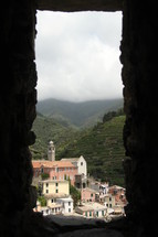 view of villas in a village through a small window opening