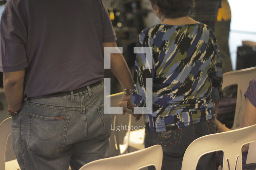 couple holding hands at a worship service