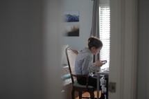 teen girl sitting at a desk texting in her room