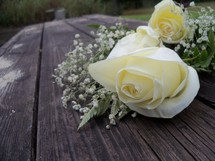 A bouquet of white roses sits on a table top making someones day on their wedding day, anniversary or special celebration.