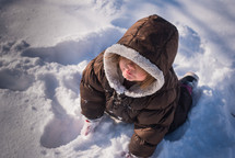 a toddler girl playing in snow