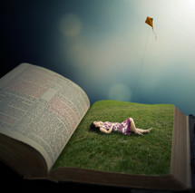 woman lying in green grass on the pages of a Bible flying a kite