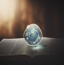 earth paperweight on the pages of a Bible