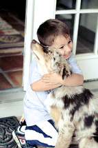 child hugging a dog