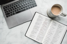 overhead view, coffee mug, opened Bible, and laptop on a table