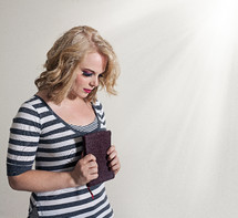 woman holding a Bible to her heart
