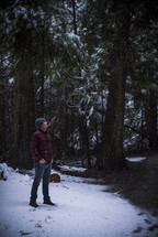 a man standing in a winter forest catching snowflakes on his tongue