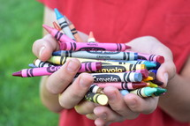 cupped hands holding crayons
