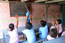 students with raised hands in a classroom
