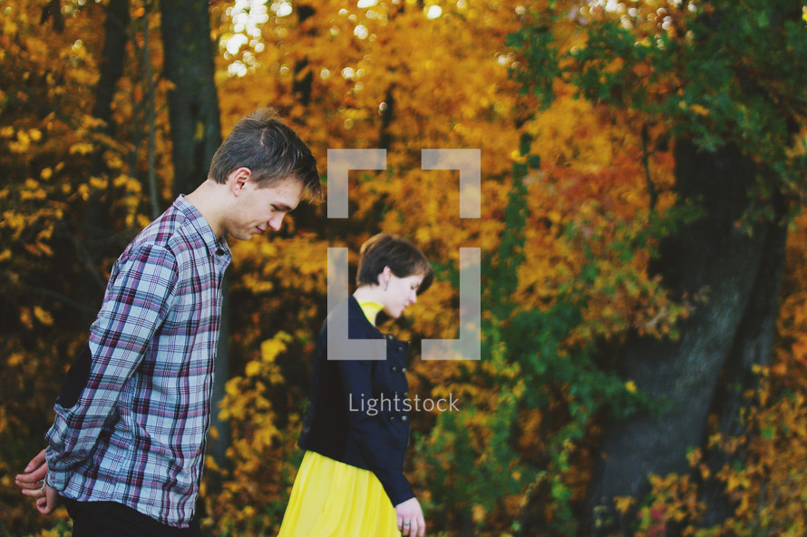 a couple walking through a forest in fall