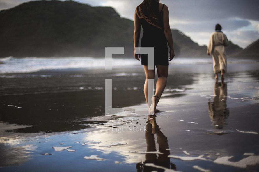 a woman following behind Jesus walking on a beach