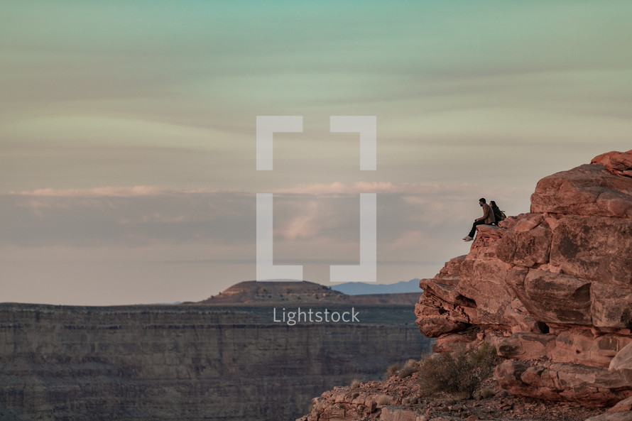 a couple sitting on a cliff at the edge of a canyon