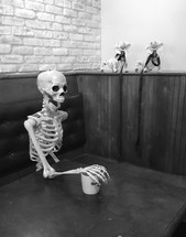 skeleton in a booth with arm on a mug