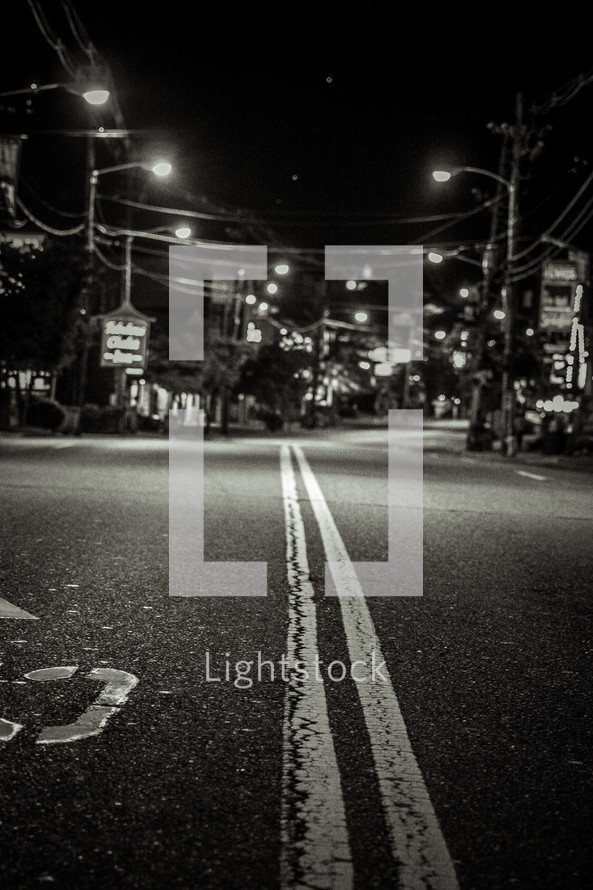 Middle of the road line through a town at night.