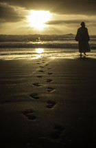 Jesus walking on a beach at sunset leaving footprints in the sand
