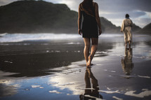 a woman following behind Jesus walking on a beach