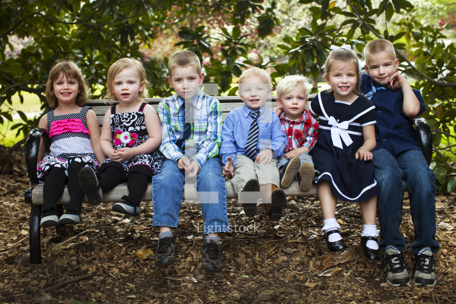 children of God sitting on a bench outdoors before church