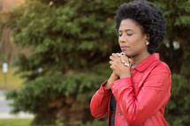 An African American woman with praying hands