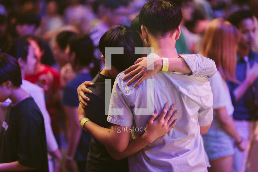 young men hugging at a worship service