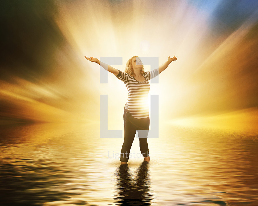 woman standing in water with her hands raised in the air surrounded by glowing light