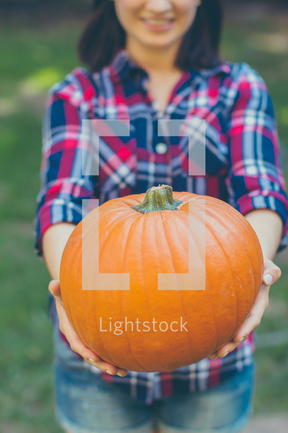 woman holding an orange pumpkin