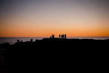silhouettes of people on a cliff over a beach at sunset