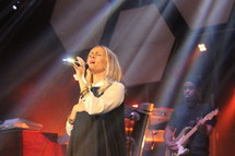 a woman singing into a microphone on stage