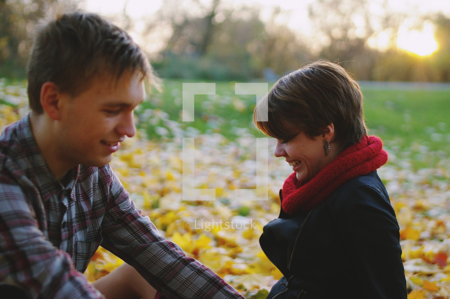 a couple sitting in fall leaves