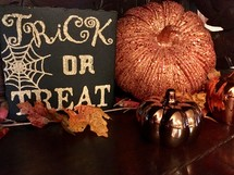 trick or treat sign and pumpkin