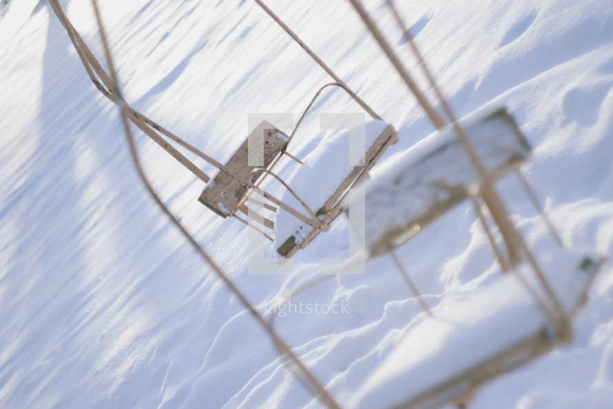 snow on ski lift chairs