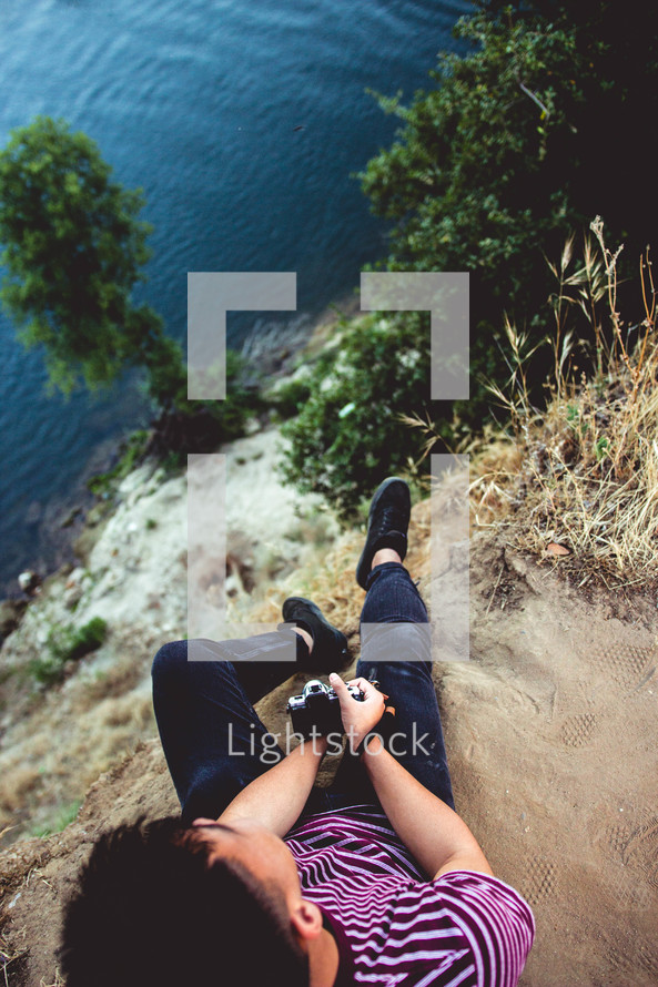 a man with a camera sitting at the edge of a cliff