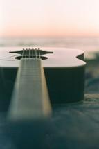 a guitar on a beach at sunset