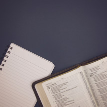 open Bible and notebook on blue background