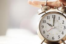 Person slamming the alarm clock off.