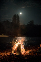 Bonfire by full-moon reflected on the river
