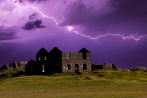 lightning in a purple sky over and abandoned house in ruins