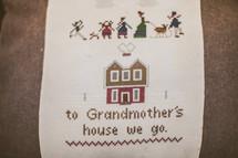 Needlepoint sampler depicting grandmother's house.