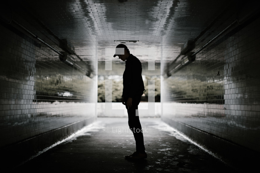 a man standing in a dark urban tunnel