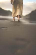 Jesus walking on a beach leaving footprints in the sand