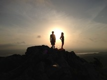 silhouette of a man and woman standing on top of a mountain