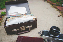 papers in an old suitcase, journal, and camera