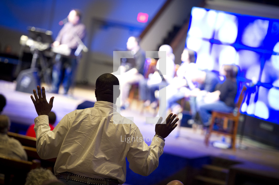 man with his hands raised in worship to God during a worship service