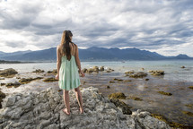 a woman standing on a rocky shore