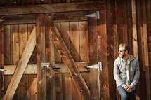 a bearded man standing by barn doors