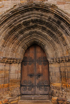 Arch over a wooden doorway of an ancient stone cathedral.