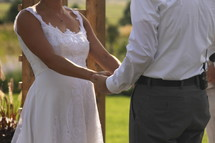torso of a bride and groom holding hands