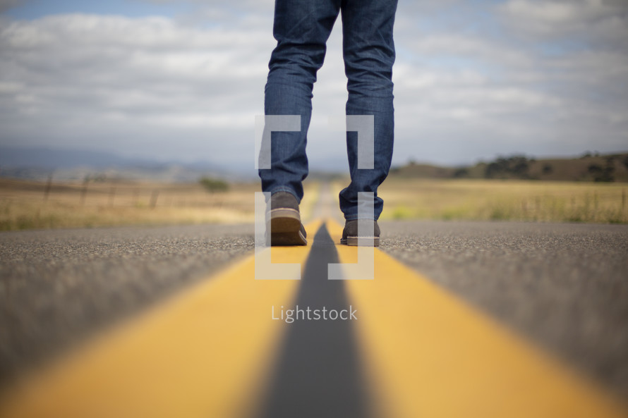 a man standing in the middle of a road