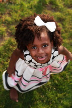 6 year old African American wearing a dress and a big bow in her hair girl looking up into the camera with a happy facial expression.